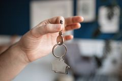 Men hand holding key with house shaped keychain. Modern light lobby interior. Mortgage concept. Real estate, moving home. House key and keychain in the form of royalty free stock images