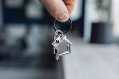 Men hand holding key with house shaped keychain. Modern light lobby interior. Mortgage concept. Real estate, moving home. House key and keychain in the form of stock photo