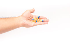 Men hand holding pile of yellow blue tablets Stock Photography