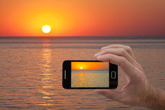 Men hand holding smart phone. With image from built-in camera of sunset Stock Photography