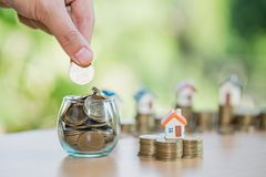 A men hand holding stacking gold coins and house model, saving m stock image