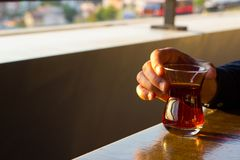 Men hand holding traditional Turkish Tea Glass during drinking it royalty free stock photos