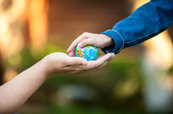 Men hand and little girl hands holding planet Earth Royalty Free Stock Image