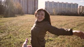 Men is hand loosens on the hand of a beautiful smiling and happy girls. Young brunette turns around in front of a man. They walk in the Park. On the horizon stock footage