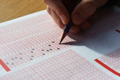 Hand with pencil filling out answers on exam test answer sheet. Men hand with pencil filling out answers on exam test answer sheet stock image