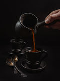 Men hand pouring the coffee in clay cup: black on the black Stock Images