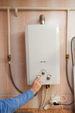 Men hand regulate the power of hot water in Gas water heater. Royalty Free Stock Image