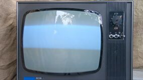The old TV is turned on by hand. Glowing Retro TV Screen Flickers On and Off