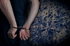 Men with handcuffs. And grunge wall in background Stock Photos