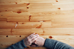 A men hands on a blank wood desk, top view at the studio. royalty free stock photos