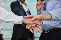 Men hands holding together in gesture of unity. Close up on men hands holding together in gesture of unity Royalty Free Stock Images