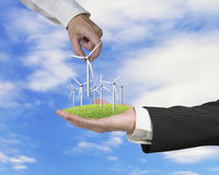 Men hands holding windturbines on meadow Royalty Free Stock Images