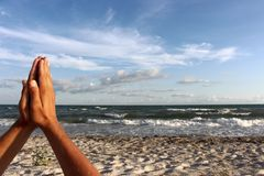 Men hands in praying sign on sand beach by the sea against blue sky with clouds. Stock Photo