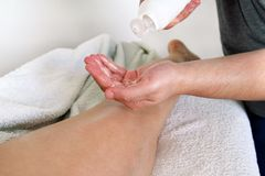 Men hands pump out of a bottle of massage oil Royalty Free Stock Photography