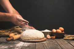 Men hands sprinkle a dough with flour Stock Photography