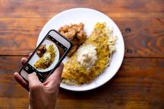 Men hands taking food photo of VENEZUELAN CACHAPA by mobile phone.  royalty free stock images