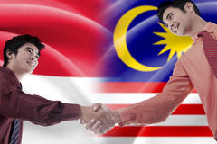 Men handshake with indonesian and malaysian flags Stock Photography