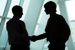 Men handshaking. Silhouettes of two businessmen handshaking and greeting each other Stock Photos