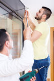 Men hang blinds Royalty Free Stock Photography