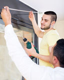 Men hang blinds Stock Photos