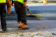 Men hard working asphalting road with shovels. Men hard working on asphalting road with shovels Royalty Free Stock Photos