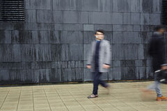 Men in haste. Hurrying men walking down trottoire along black wall of modern building royalty free stock image