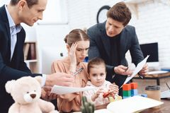 Men have a complaint about a woman who came with her daughter to work. stock photos