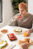 Men having breakfast with toasts at table stock photography