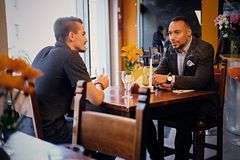 Men having a business meeting in a restaurant. Caucasian and black American men having a business meeting in a restaurant Stock Image