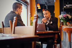 Men having a business meeting in a restaurant. Caucasian and black American men having a business meeting in a restaurant Stock Photography