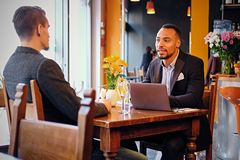 Men having a business meeting in a restaurant. Caucasian and black American men having a business meeting in a restaurant Royalty Free Stock Photo