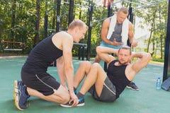 Men having calisthenics workout. Fit young men having calisthenics workout with friends royalty free stock image