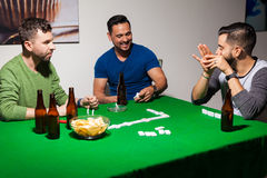 Men having fun during poker night. Portrait of a group of three men drinking some beer, laughing together and playing dominoes at home Royalty Free Stock Photography