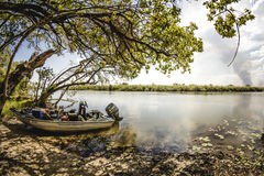 Men having a rest deep in the shadow of the trees, after navigating the Okavango Delta, Botswana. Fisherman having a rest after navigating deep inside the Stock Photo