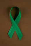 Men healthcare concept. Green awareness ribbon on brown background. Symbol of Mental Health Stock Images