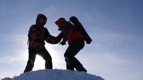 Men help each other to conquer summit of a high snowy mountain by holding hands and stretching each other to top at. Men help each other to conquer summit of stock video