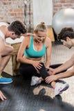 Men helping an injured woman at gym Stock Image