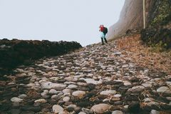 Men hiker with backpack on the scenic coastal road. The route leads along huge volcanic rock cliffs above roaring ocean Stock Image