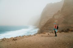 Men hiker with backpack on the scenic coastal road. The route leads along huge volcanic rock cliffs above roaring ocean Stock Photos