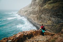 Men hiker with backpack on the scenic coastal road. The route leads along huge volcanic rock cliffs above roaring ocean Royalty Free Stock Photo