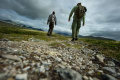 Men hiker walking towards mountain. PIcture of a two hikers walking stock photos