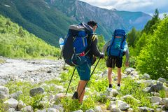 Men hiking in mountains. Trekking in mountain trail. Adventure in wild highlands of Italian Alps mountains royalty free stock photo