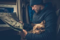 Men and His Dog Friend. Australian Silky Terrier York Relaxing on the Traveling Men Legs. Traveling Pet in the Class B RV Motorhome Camper Royalty Free Stock Image