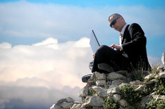 Men with his laptop. Working on a stone wall royalty free stock photos