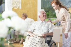 A man in his old age ia a wheelchair talking to a personal assistant in a common room of a rehabilitation center. A men in his old age ia a wheelchair talking royalty free stock photography