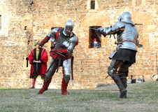 Men in historical battle. Fighters having battle in sword and historical renaissance costume in front of the castle wall on the performance of the Svihov battle Stock Photo