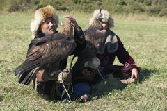 Men hold golden eagles (Aquila chrysaetos), Almaty, Kazakhstan. Stock Photography