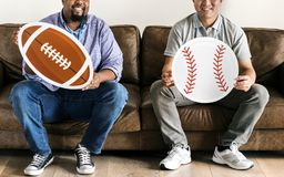 Men holding baseball and rugby icons sitting on couch Royalty Free Stock Photography