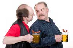 Men holding a beer belly and sausage. Elderly men holding a beer belly and sausage Stock Photography