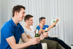 Men holding beer bottles cheering Stock Images
